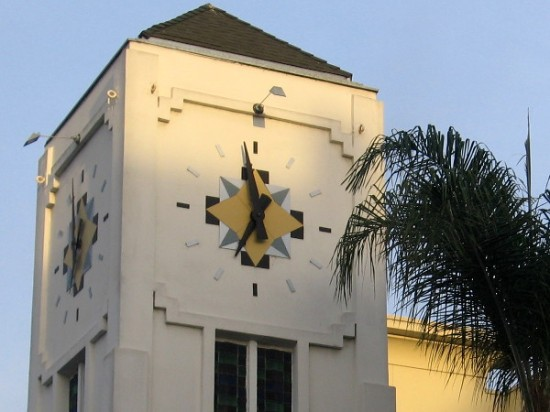 Eye-catching clock atop tower on a street corner.