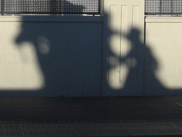 Waiting at Little Italy trolley station, I see a strange shadow climbing up the opposite wall.
