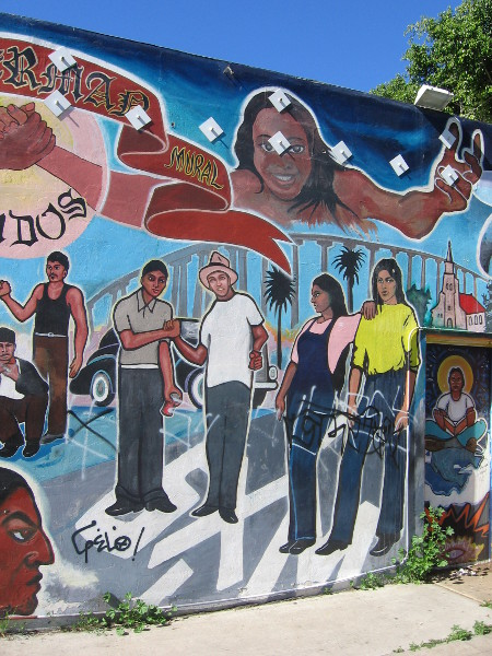 Words above people read Barrio Sherman Mural Unidos.