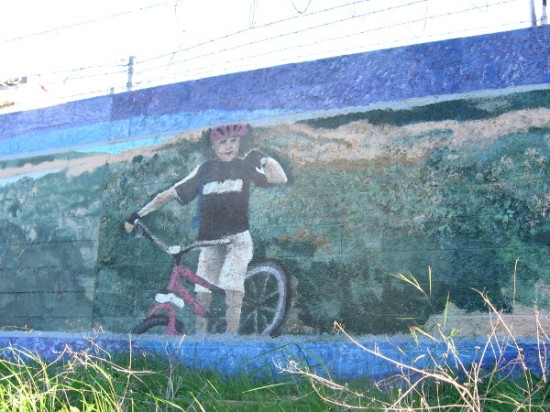Happy painted bicyclist greets those who travel down San Diego River Trail.