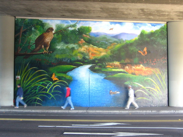 Pedestrians file past artwork that shows nearby San Diego River and wildlife.