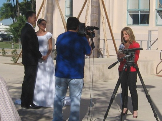 This soon-to-wed couple is interviewed by a television reporter.