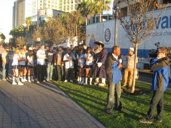 Television news people, the Pad Squad and fans watch Padres begin move to Spring Training.