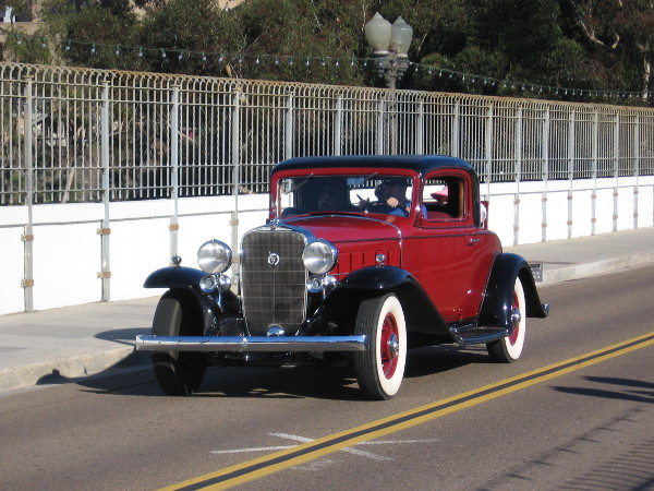 Classic automobile cruises over San Diego's scenic Cabrillo Bridge.