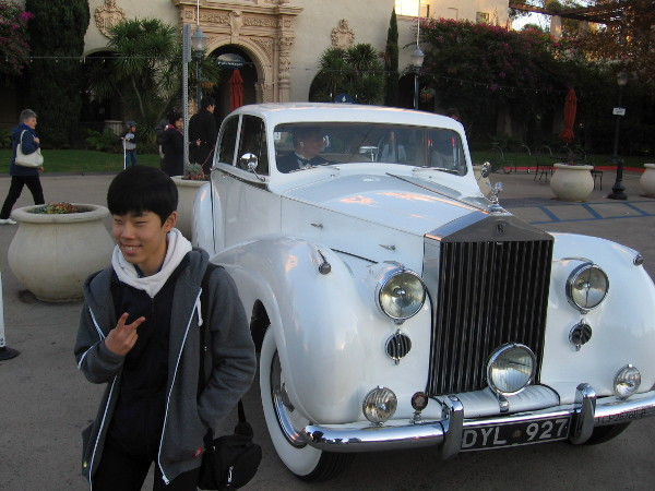 Someone poses for a photo by Rolls Royce limo standing by in Balboa Park.