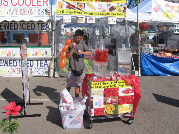 Young man selling treats pumps up a balloon.