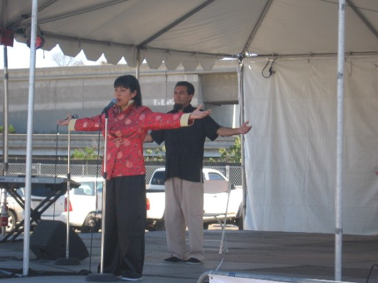 Lady demonstrates Chi Gong stretches on a large stage.