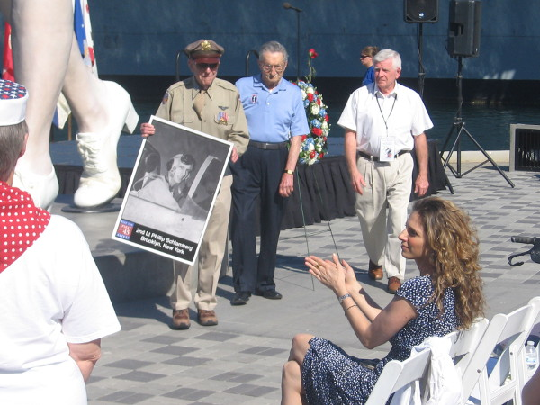 After presenting the first wreath, photo of last American killed during World War II is carried by a hero.