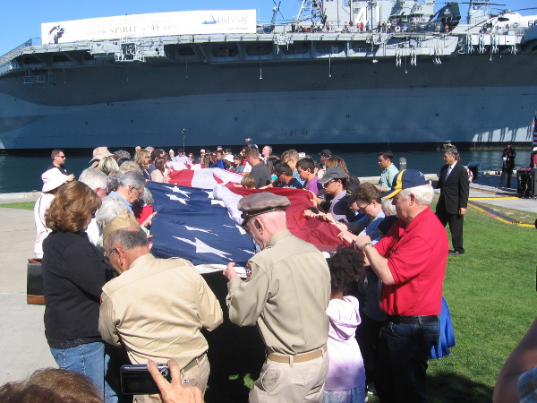 Many hands get ready to unfurl the huge flag on the grassy area between the Unconditional Surrender statue and Bob Hope Tribute.