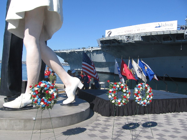 Photo of three wreaths and flags after the crowd has dispersed.