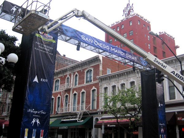 Putting up big Mardi Gras arches along Fifth Avenue in San Diego's Gaslamp.