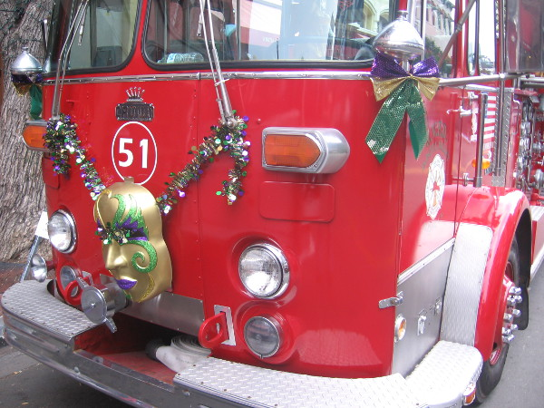 Three old firetrucks were decorated with Mardi Gras masks and ornaments.