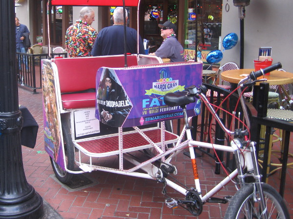 This pedicab is covered with Fat Tuesday ads and flashing lights.