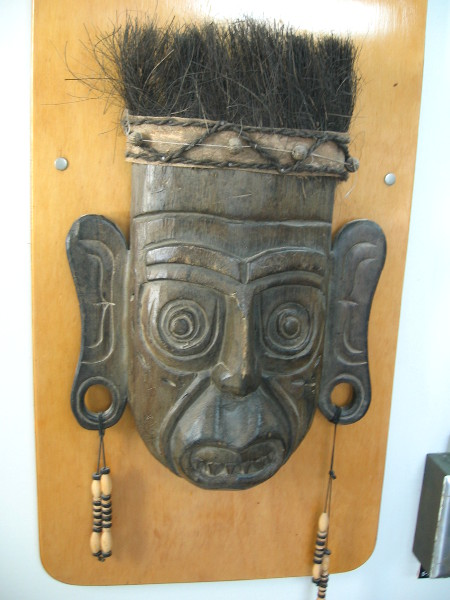 Several masks, ethnic artifacts and marine objects decorate the walls of the cafeteria.