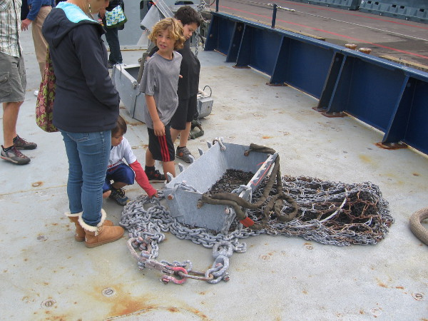 Kids examine a rock dredge, used for the recovery of heavy material on the ocean floor.