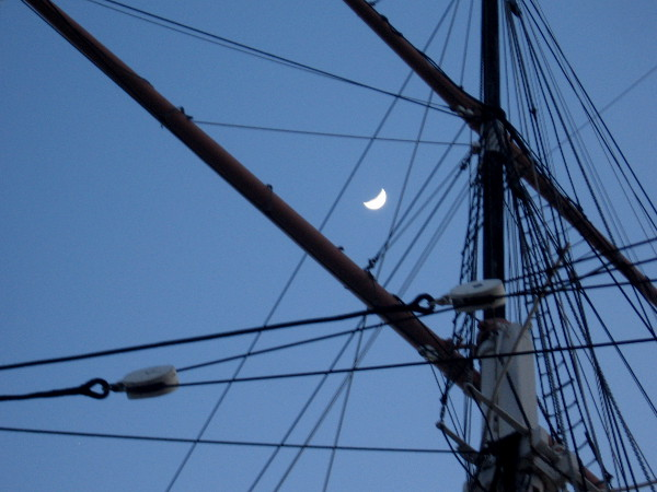 Moon behind a mast and yards of San Diego's historic 1863 bark Star of India.