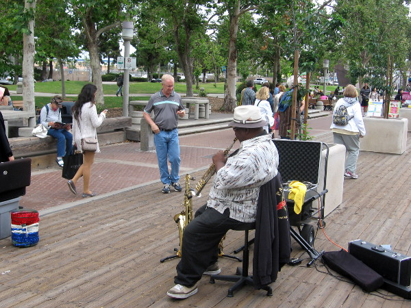 People staring downward and street musician near USS Midway.