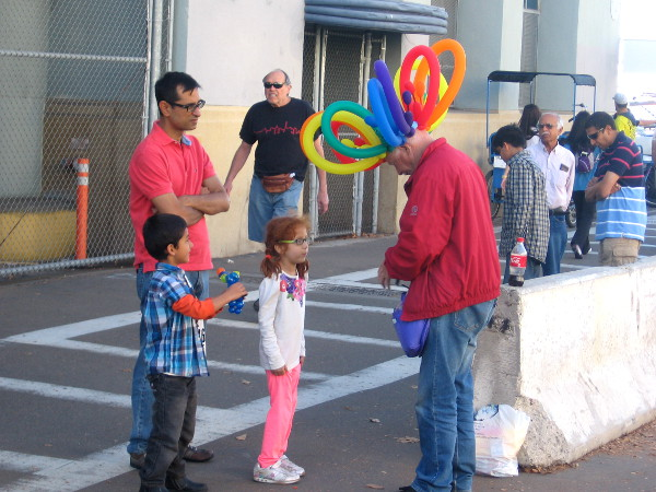 Adults seem preoccupied as balloon twister guy creates colorful fun for kids!