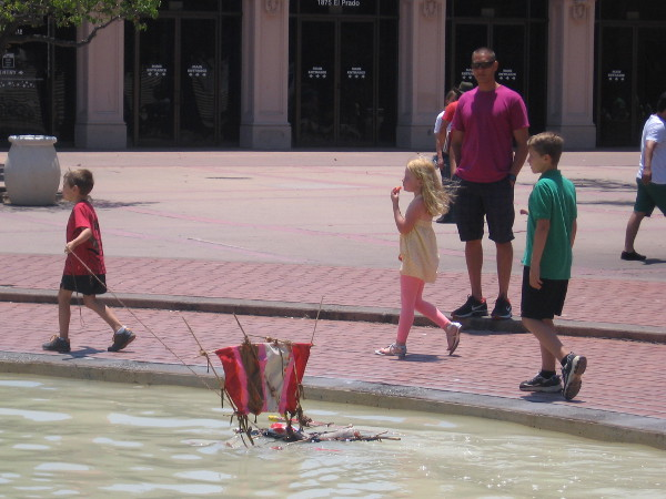 Kid tows handmade boat over cloudy water in the circular fountain basin.