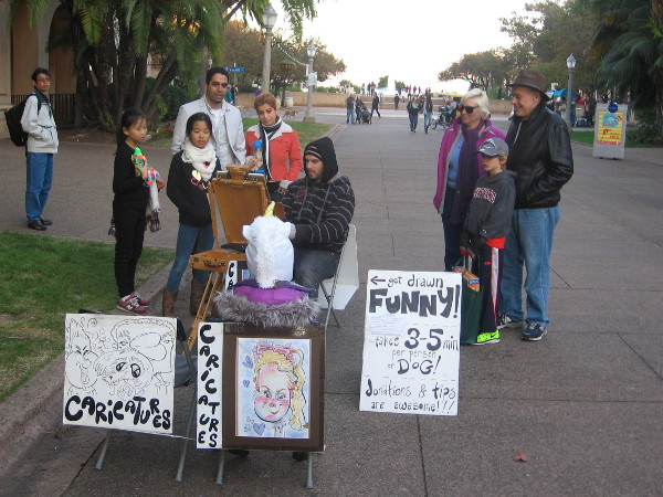 A caricature artist at work on El Prado as folks watch.