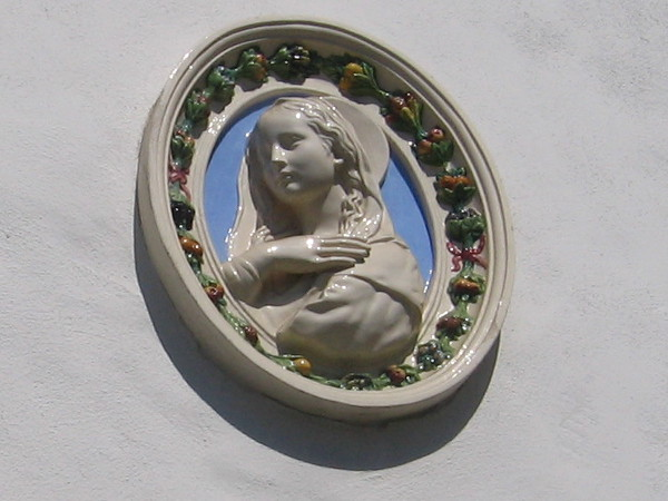 Medallion-like artwork on wall above the Italian Cultural Center sign.