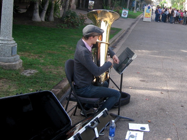 Playing a horn, trying to draw a crowd.