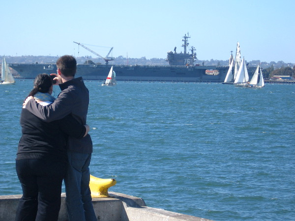 Couple takes a selfie on a beautiful day as sailboats glide past USS Ronald Reagan.
