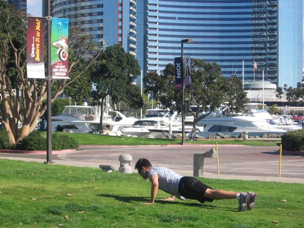 Man doing a few public push-ups on grass in Embarcadero Marina Park North.