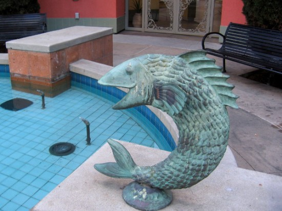 Metal fish sculpture seems to leap from Piazza Villaggio fountain.