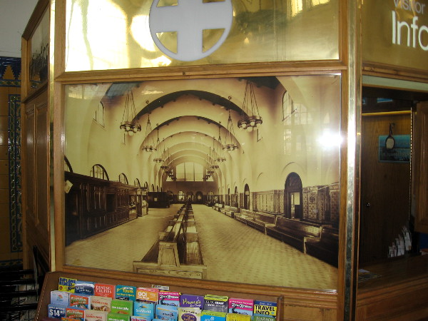 Old photo on today's information booth shows large waiting room as it was once configured, with ticket counters, checkroom and shops in wooden structures on the west side.
