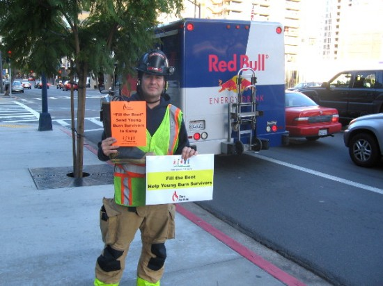 At corner of Ash and Front Street, a San Diego firefighter volunteers to collect donations to assist burn victims.