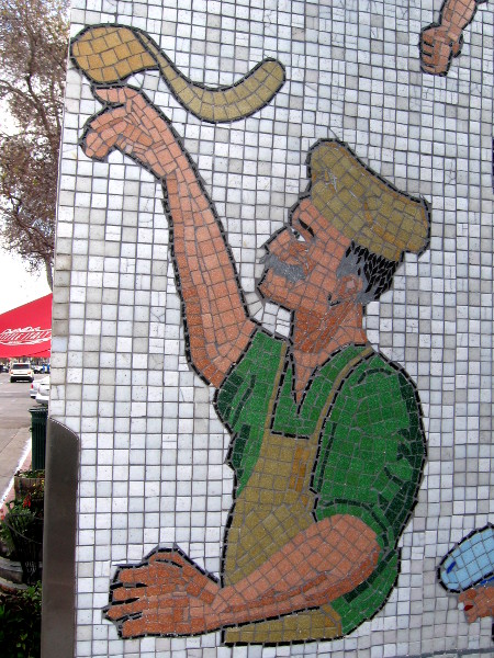 Chef tosses a mosaic pizza at base of artistic Little Italy Landmark Sign.