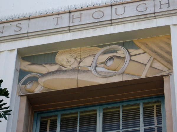 Art Deco relief work shows female above propellers of airplane.