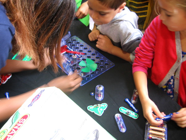 Kids learn about electronics by combining fun pieces from a kit, creating circuits.