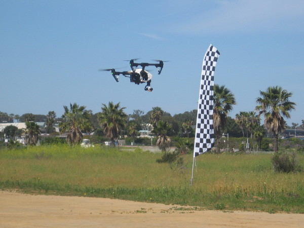 A quad hovers above the special flying area on a breezy day near Mission Bay.