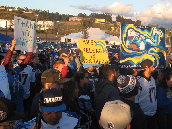 Handmade signs express hope that Chargers football remains in San Diego.