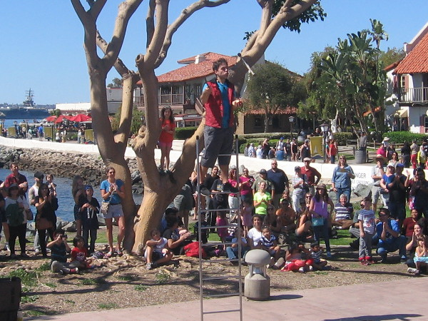 Alex Clark, with training from Cirque Du Soleil, balances atop ladder while juggling knives.