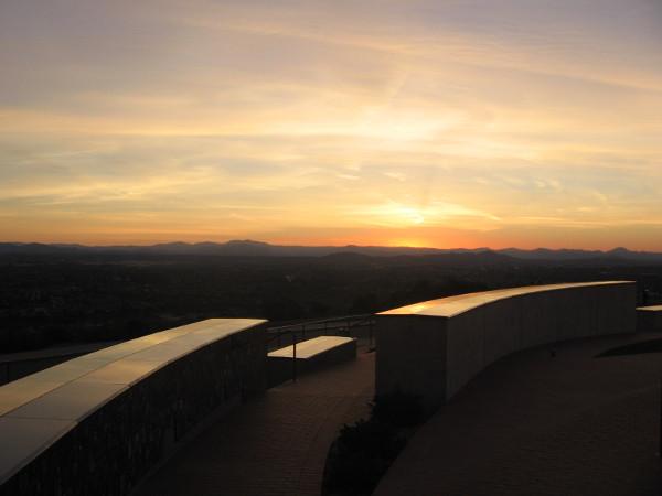 Sun rising on eastern horizon illuminates top of concentric walls of the memorial.