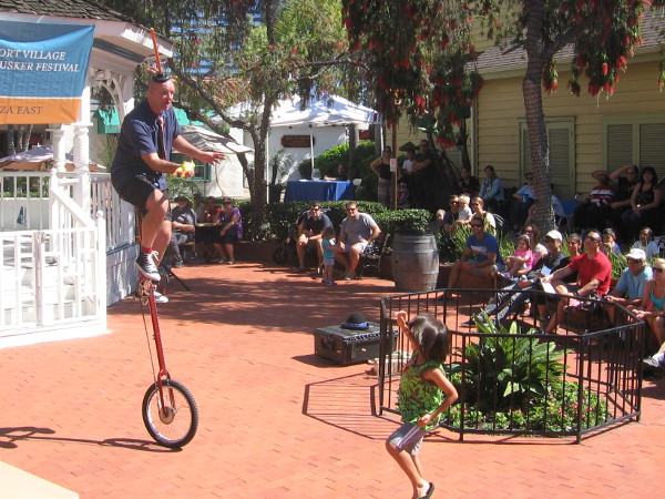 Girl throws rubber chicken up to plunger-headed, unicycle-riding Groovy Guy Collins, who has starred on the Travel Channel.