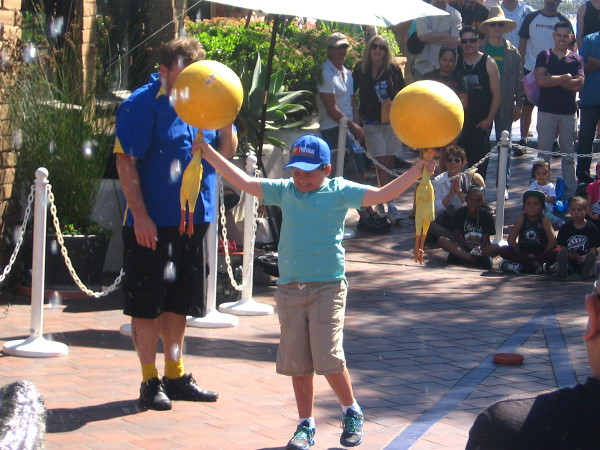 Boy volunteer balances two spinning balls atop two rubber chickens!