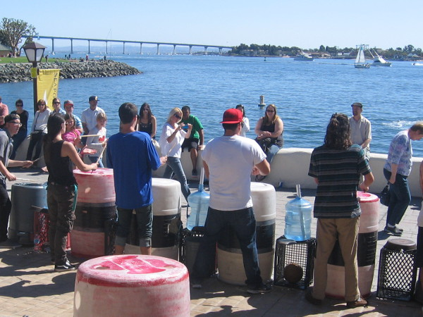 Unusual instruments produce fun beats as busker festival visitors sit in sunshine by San Diego Bay.