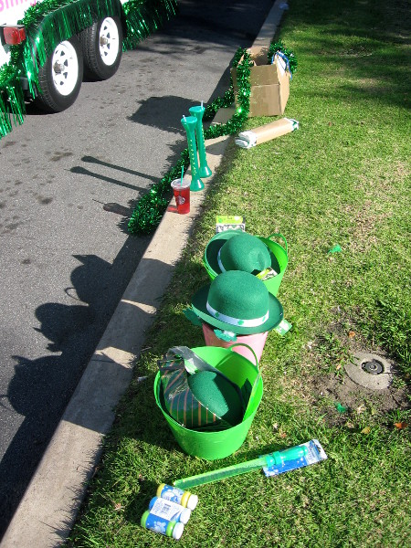 Fun green hats and stuff line the grass by the sidewalk.