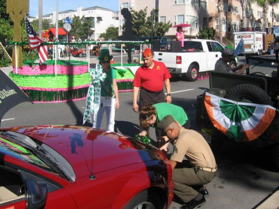 Serviceman helps affix some green to the front bumper of a car.