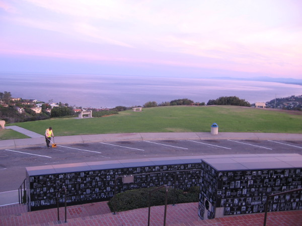 Gazing over curved walls containing memorial plaques toward the Pacific Ocean in morning light.