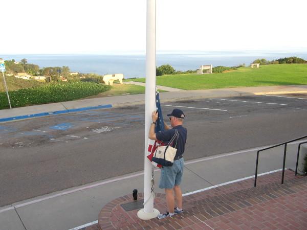 Veteran volunteer prepares to proudly raise the American flag.