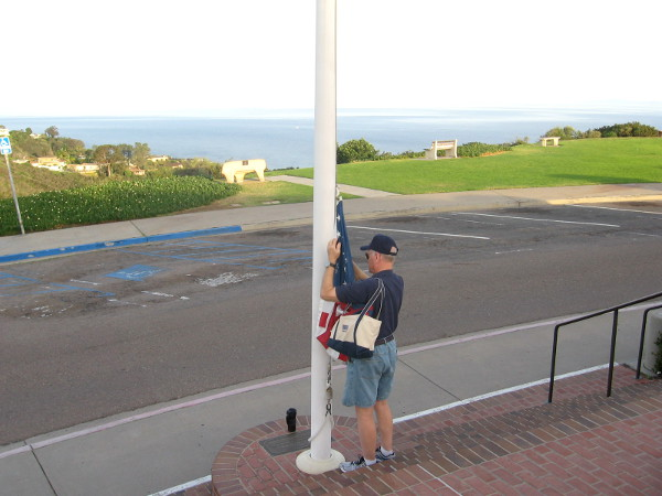 Veteran volunteer prepares to proudly raise the American flag.