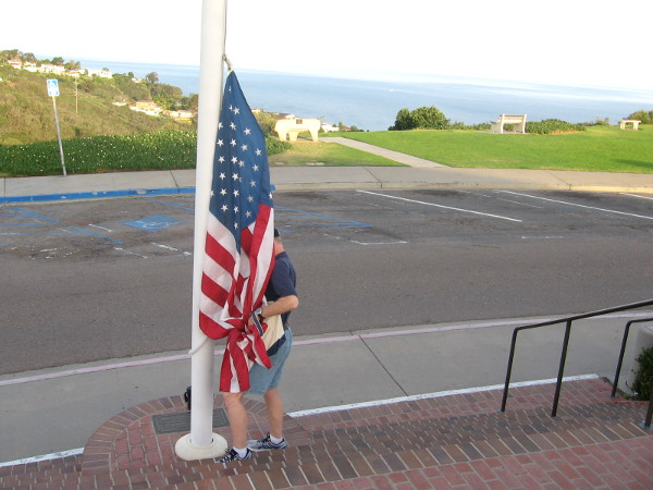 The Stars and Stripes is carefully attached, ready to be lifted into the wide, blue sky.