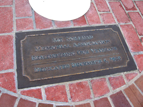 Plaque at base of flagpole.