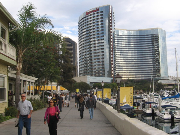 People walk near the Marriott Marina on the sun-drenched Embarcadero.