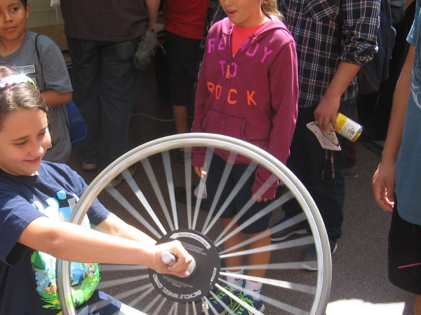 Girl learns about gyroscopes and angular momentum with a spinning bicycle tire.